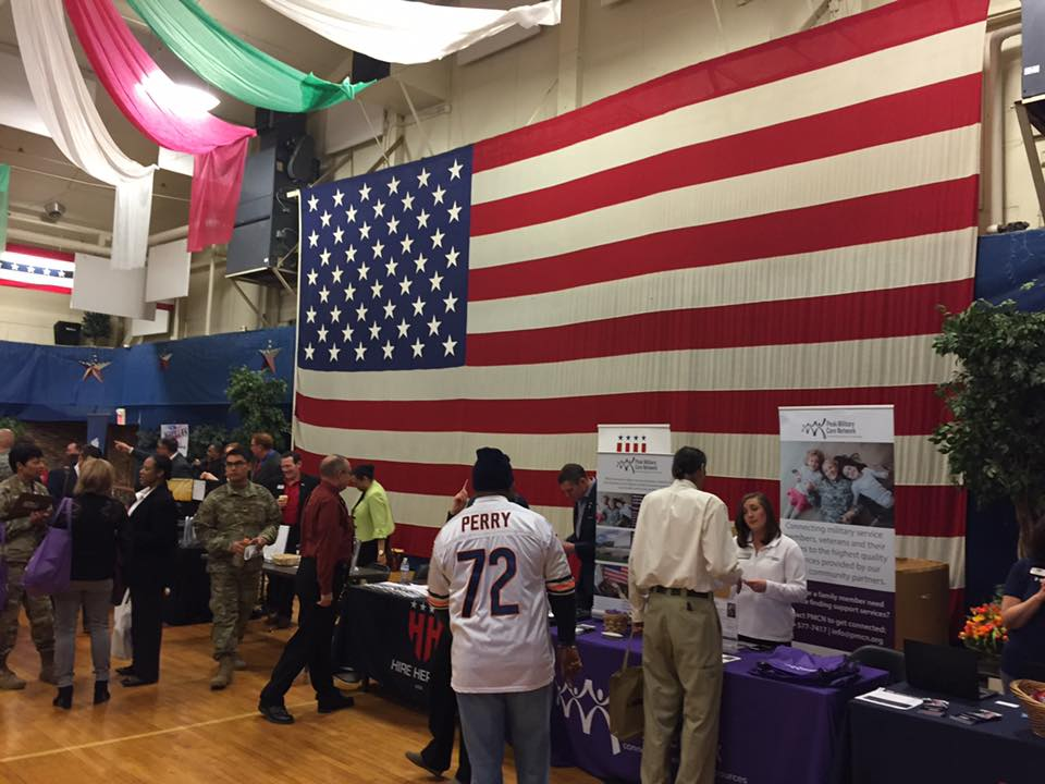 People at job fair booths in front of an American flag